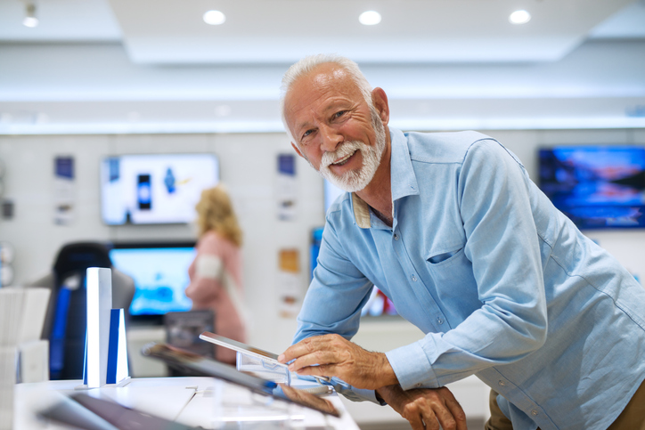 Senior bearded man looking at camera and trying out tablet while leaning on stand.