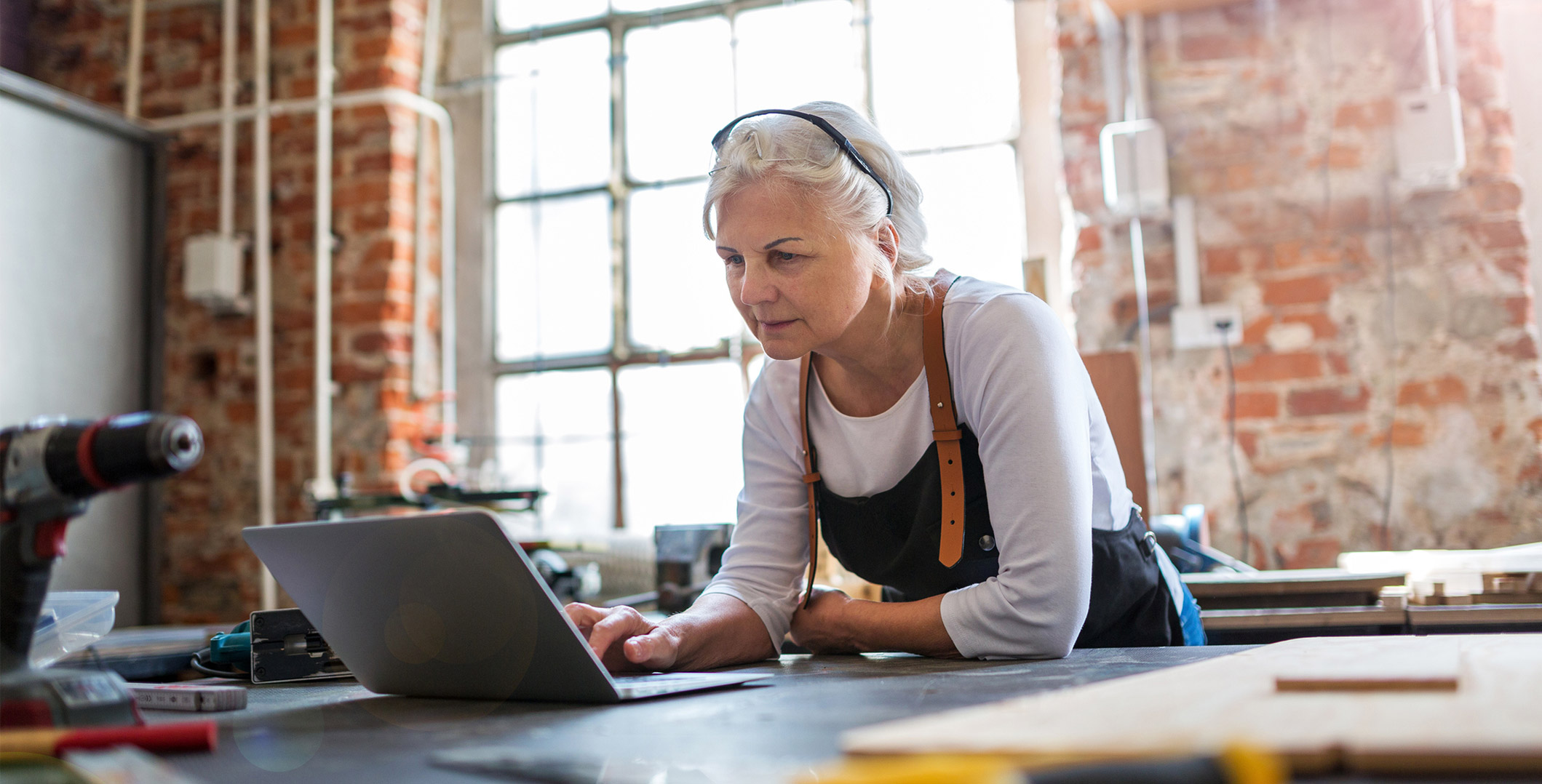 Older lady working with laptop and various tools